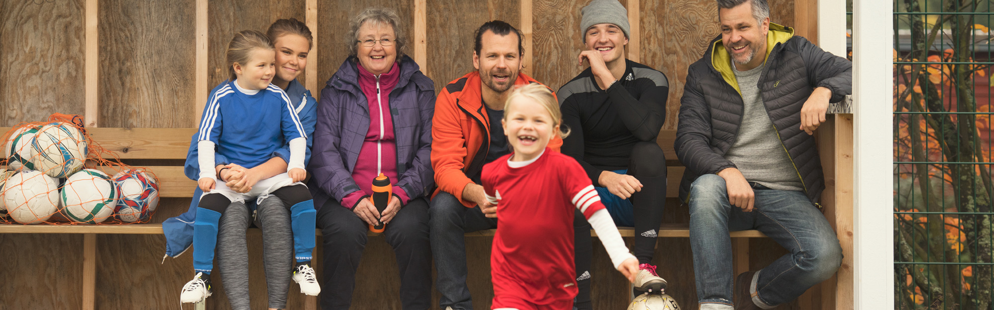 A group of people watching a kids soccer game.