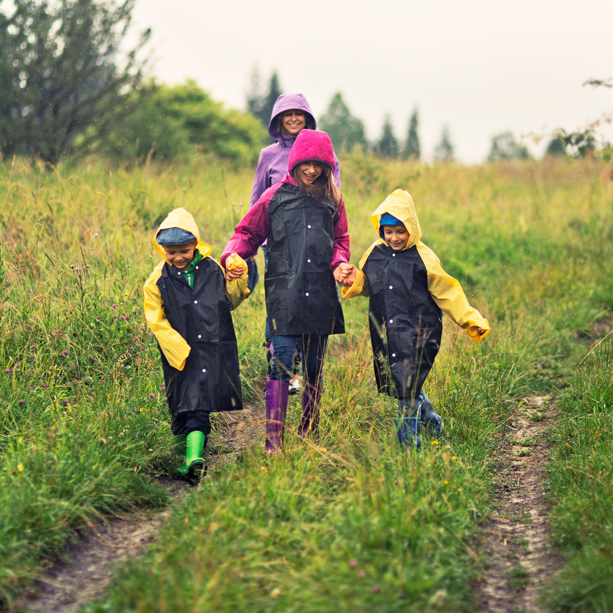 A family outdoors with raincoats on.